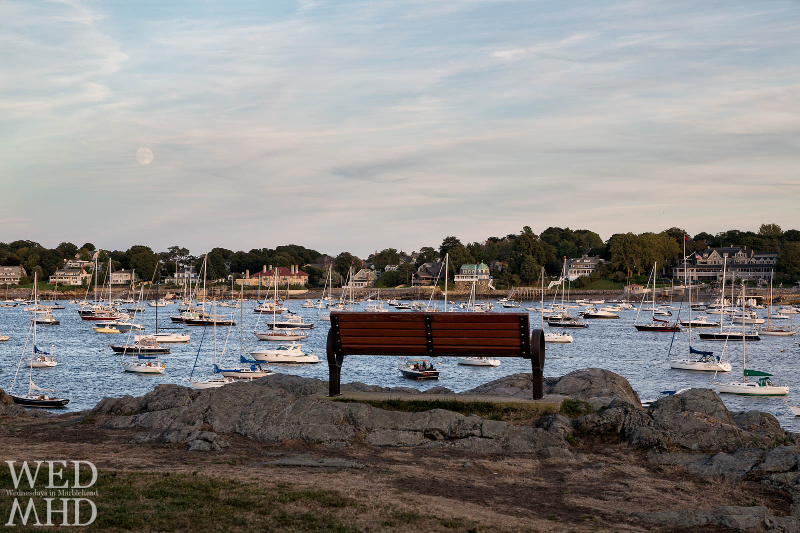 A bench on the rocks at Crocker Park is the best seat in town for watching the sun and moon rise over Marblehead harbor