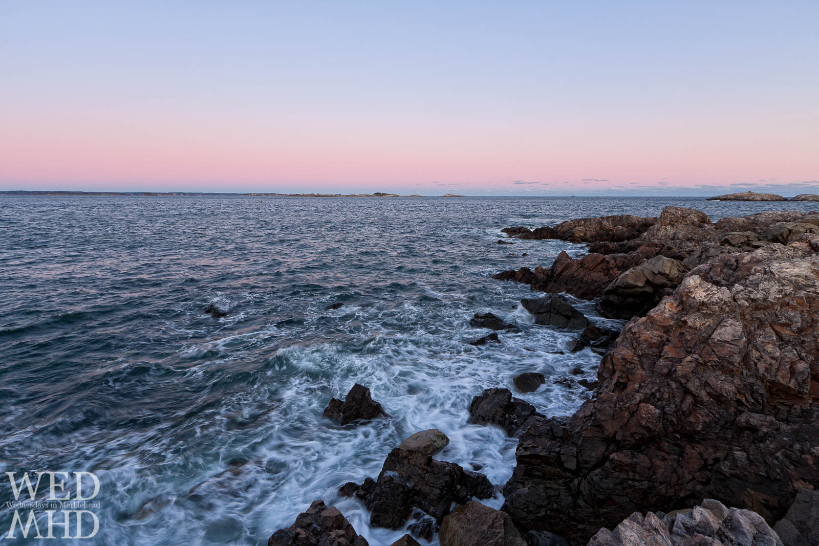 The ocean water churns along the rocky shore of Chandler Hovey Park at sunset