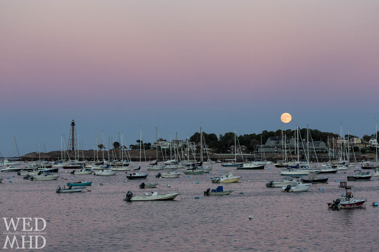The full harvest moon is captured on a late September evening over Marblehead Neck appearing as a Corinthian moonrise with the yacht club just under the glowing light
