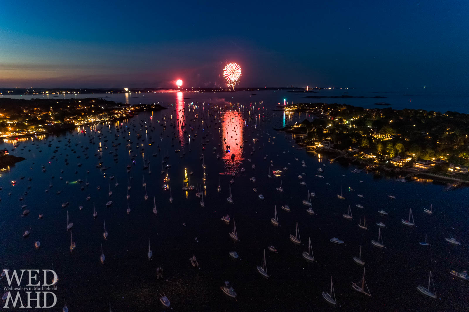 An aerial view of fireworks over Marblehead Harbor to celebrate Independence Day. The boats and lighthouse make for a picture perfect Marblehead fourth of July.
