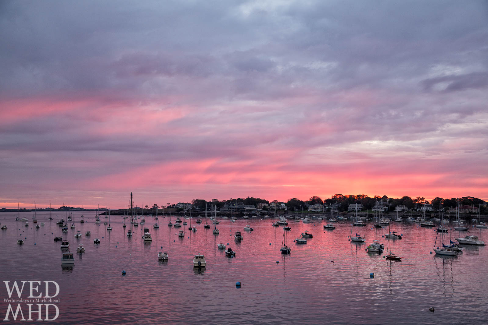 An October sunrise bathes Marblehead harbor in perfect pink light.