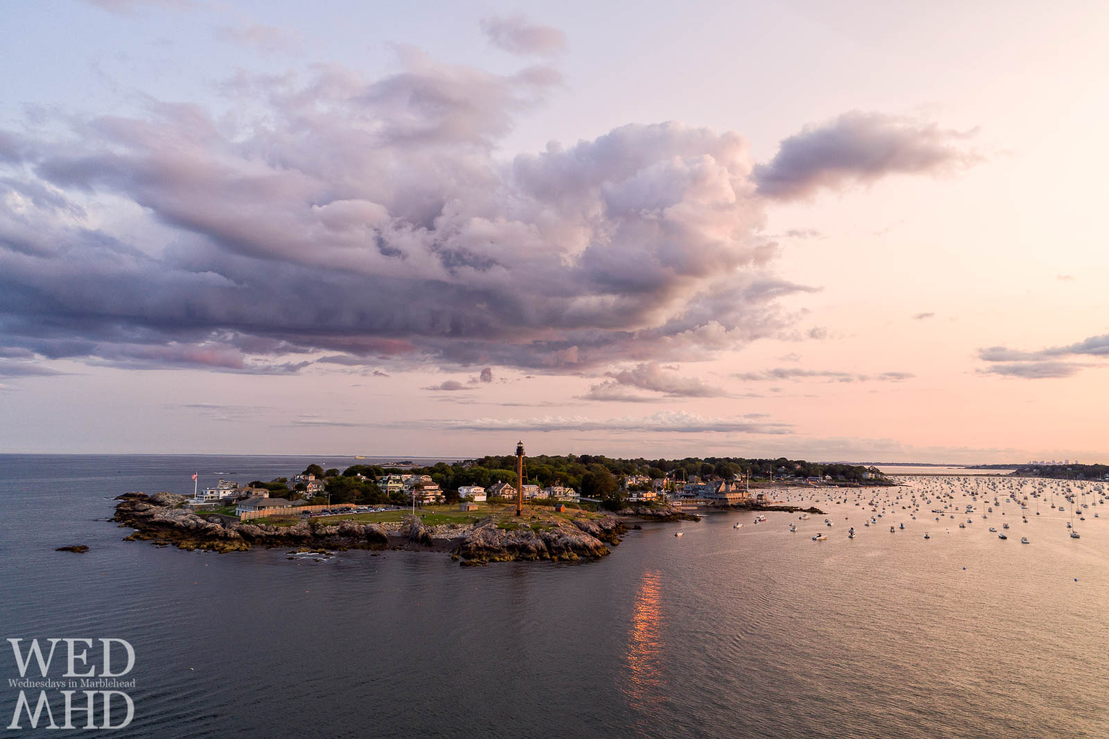 An aerial image captures the setting sun reflecting off a house on the Neck with Marblehead Light standing tall over the homes and foliage