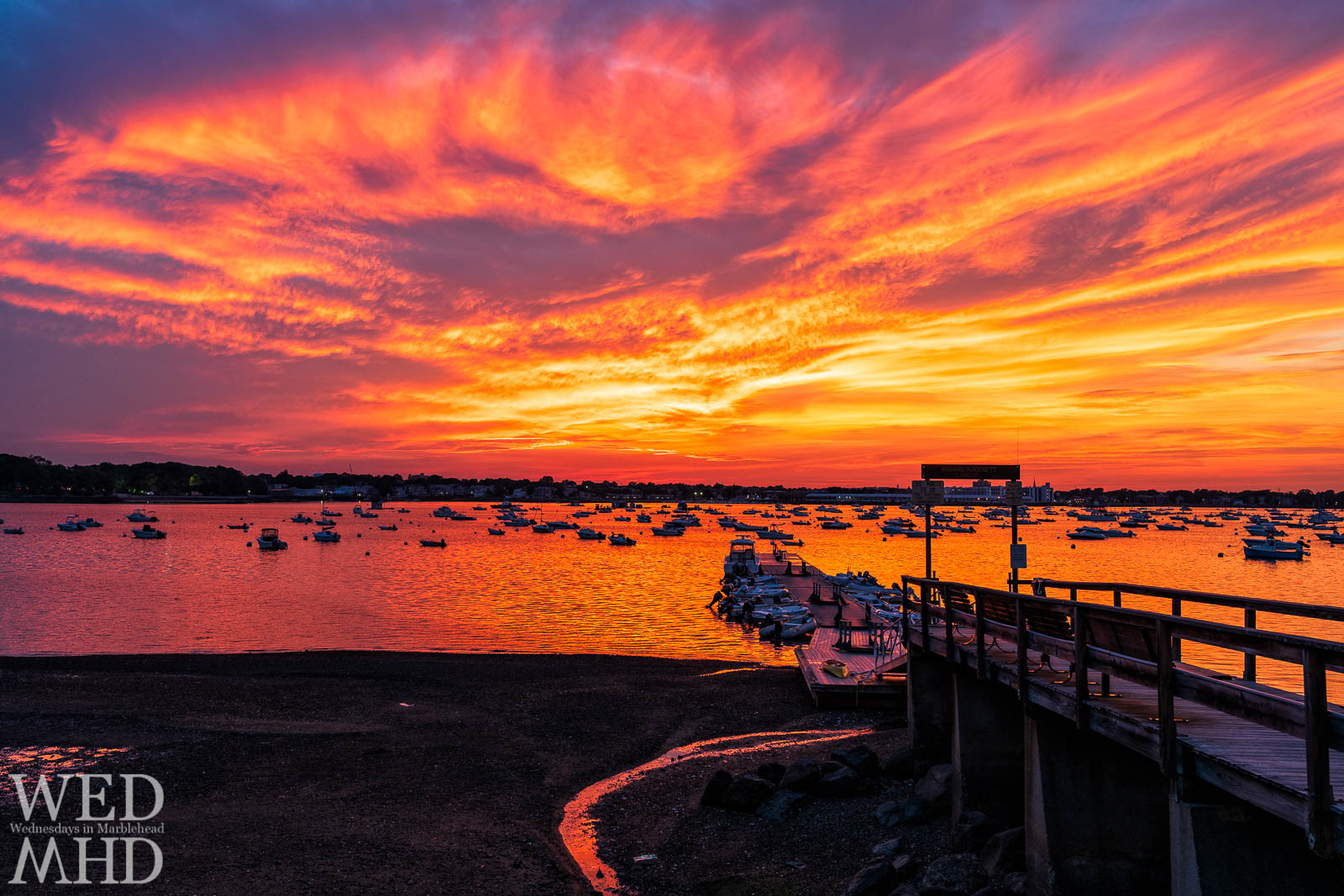 Hot and humid air from the coming heat wave erupts as a fire in the sky over Salem harbor and the Village Street pier at sunset