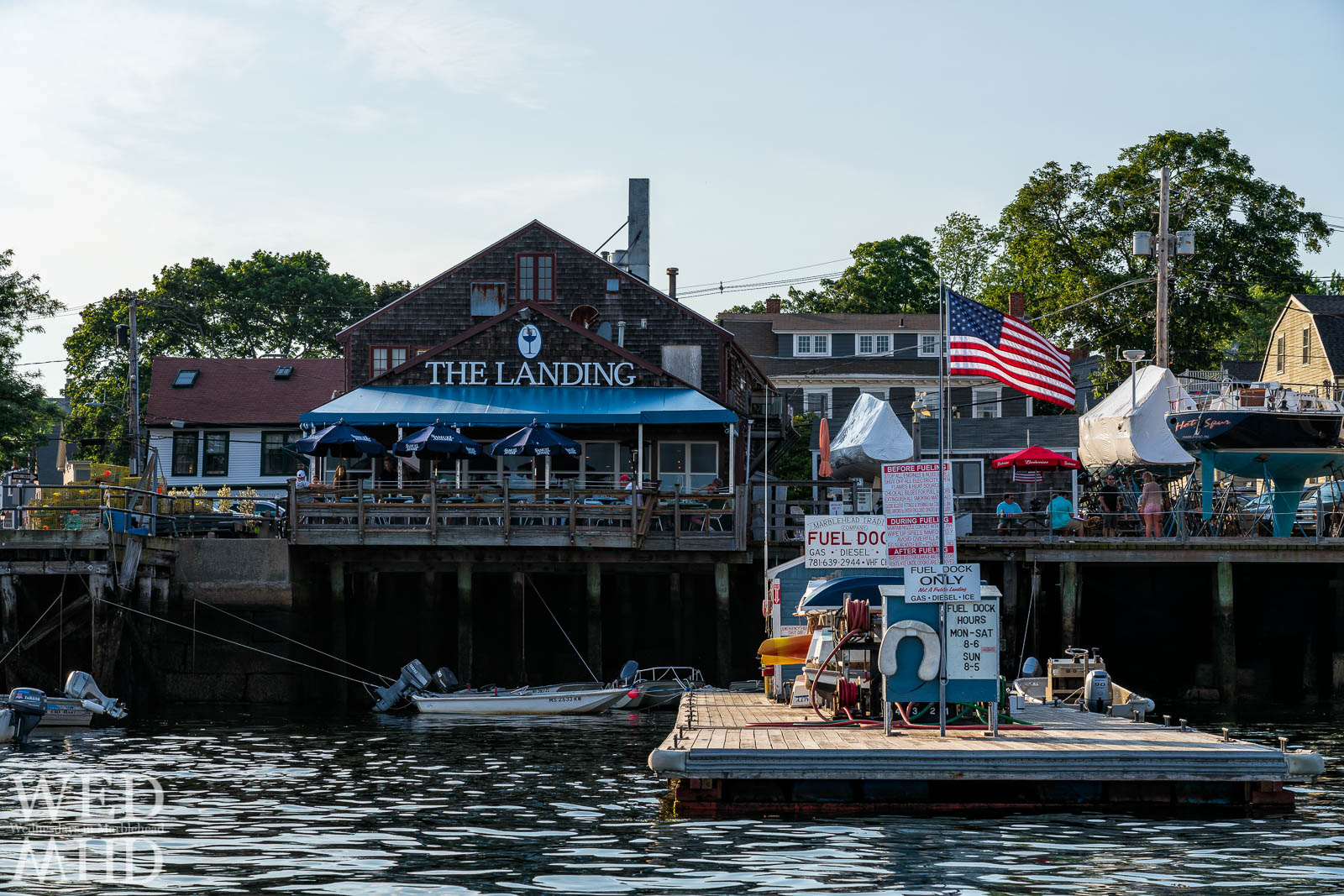 A backlit flag waves over the Marblehead Trading Company fuel dock while people are seen fueling up themselves at the Landing in Marblehead