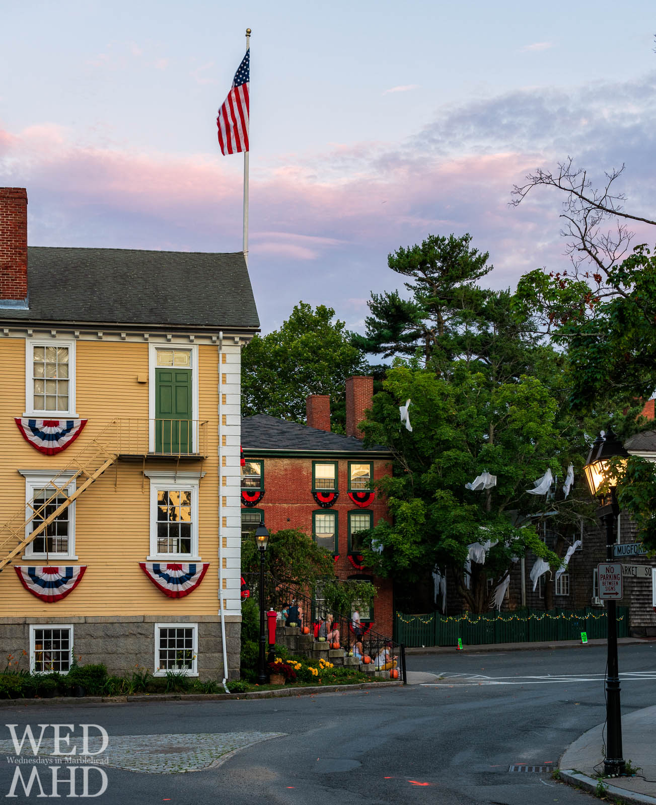 Old Town House is bathed in the light of sunset with ghosts in the trees bringing a Halloween atmosphere to a mid-July evening in Marblehead