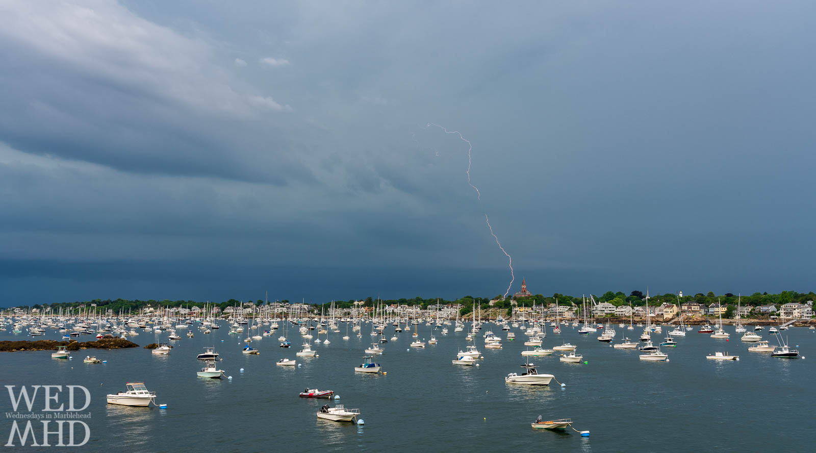 The first summer storm in Marblehead brings a bolt of lightning near Abbot Hall and over a harbor filled with boats