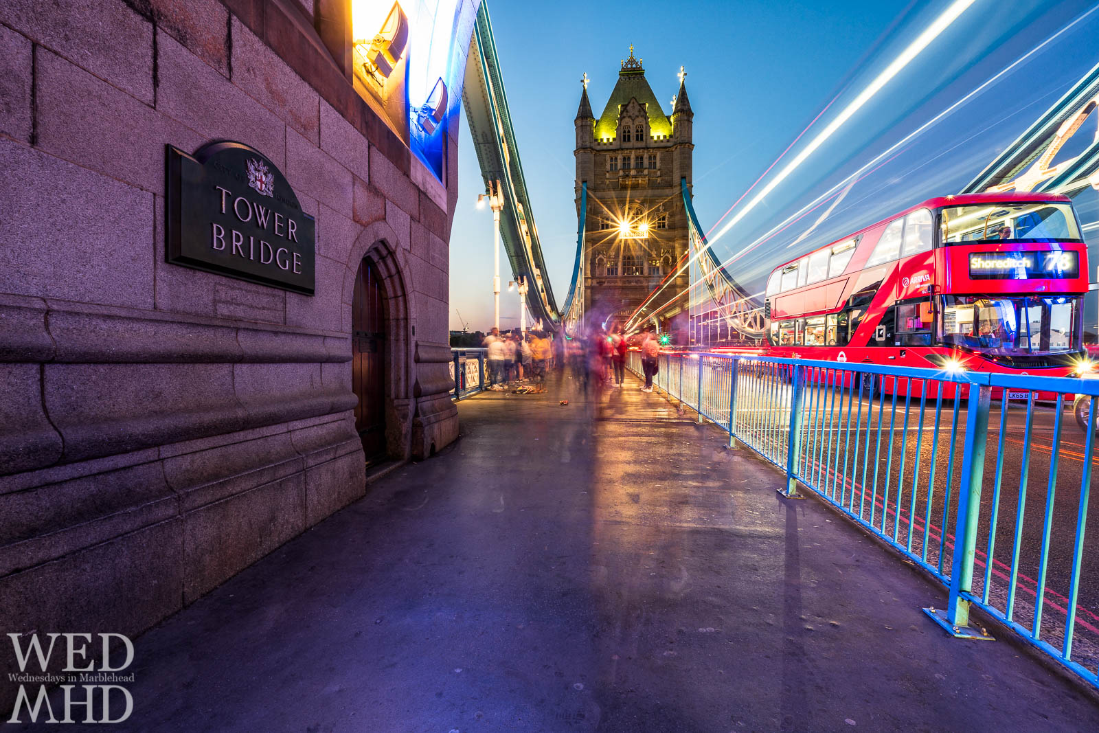 Tower Bridge is captured in a long exposure on a summer evening to highlight the traffic lights and a stopped red bus from Shoreditch