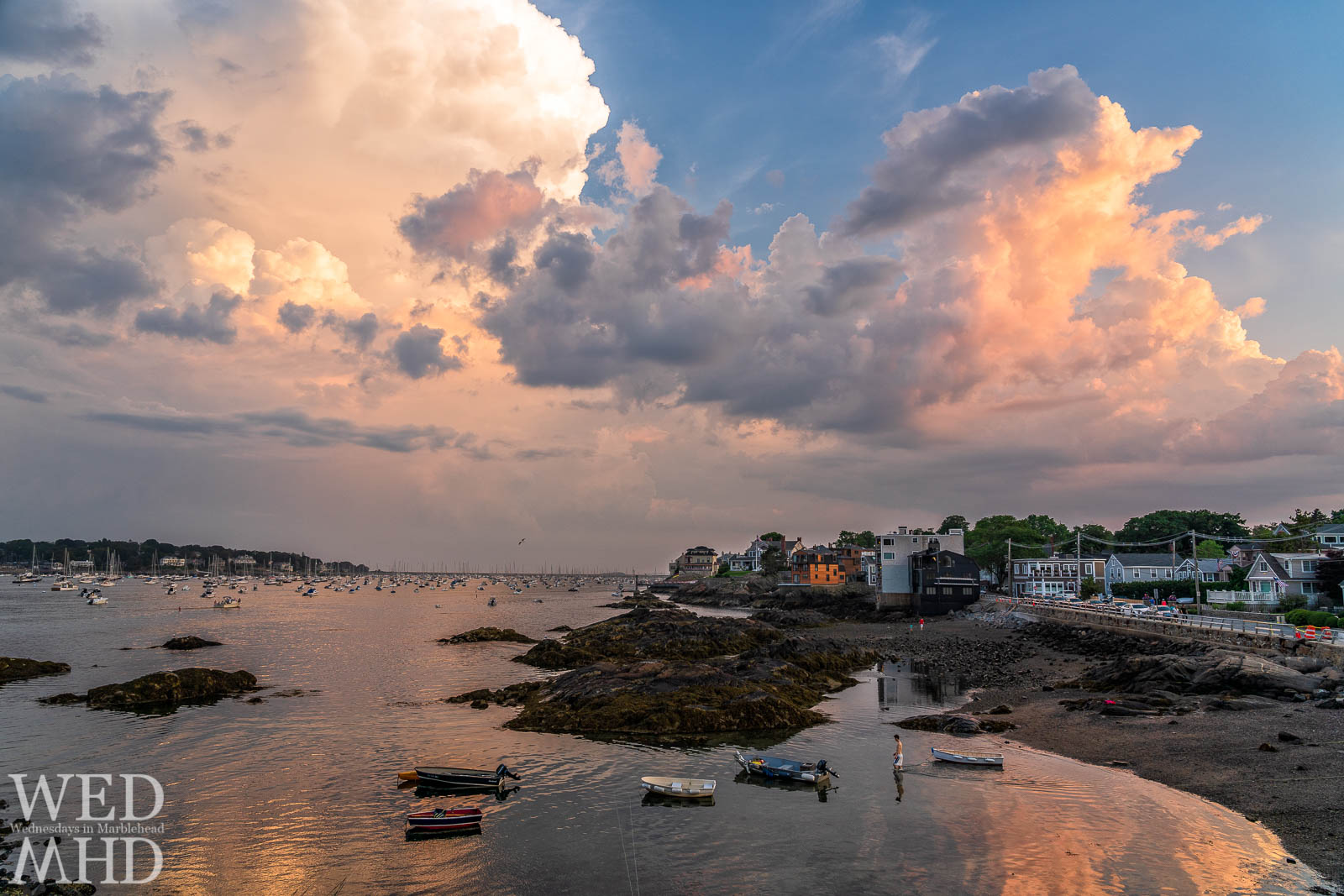 The sky erupts in color creating a beautiful Fort Beach sunset with the light reflecting off the calm water of Marblehead Harbor
