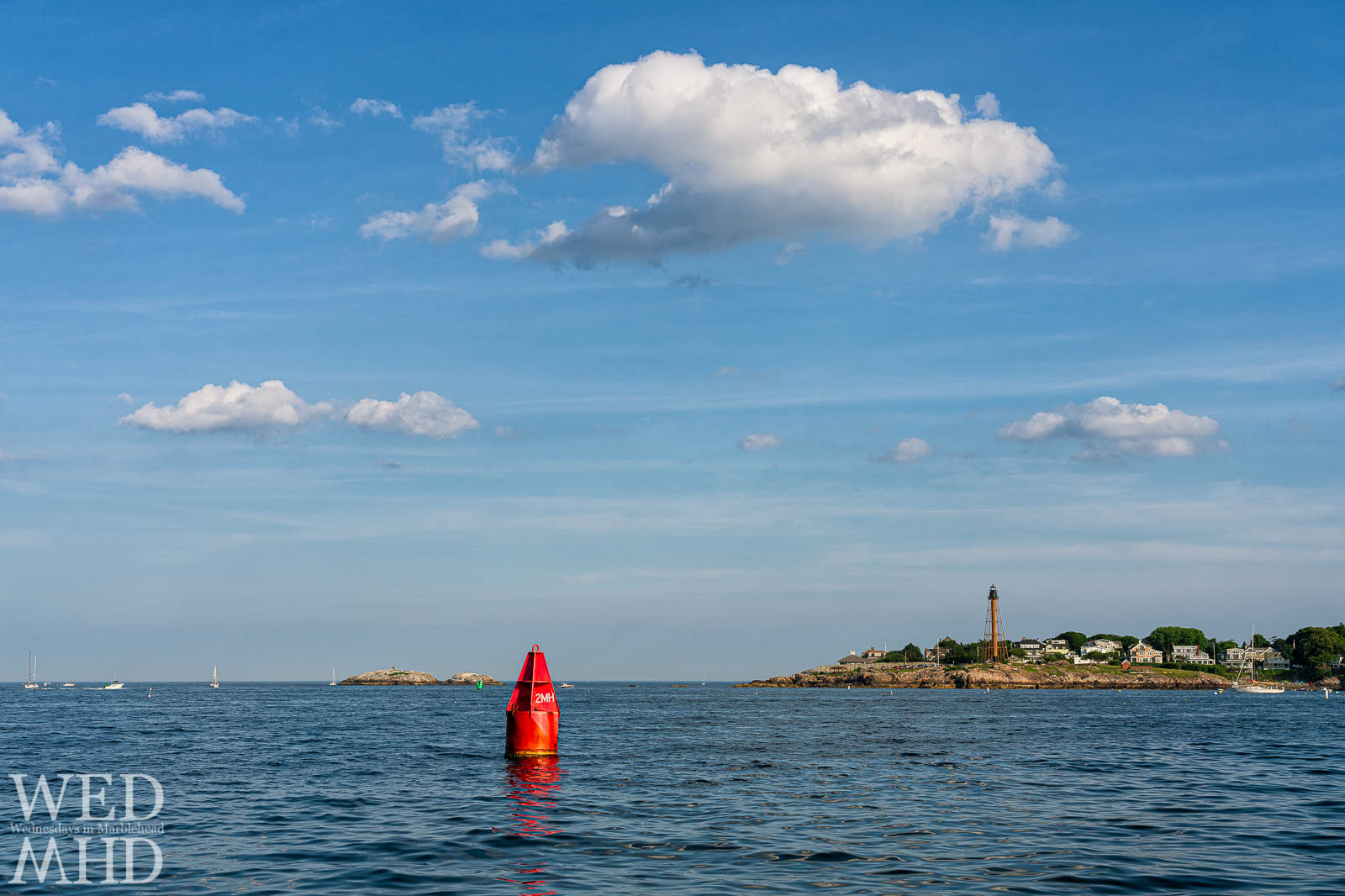 A red channel marker labeled 3MH is captured marking the harbor entrance into Marblehead with the lighthouse on Chandler Hovey Park in the background