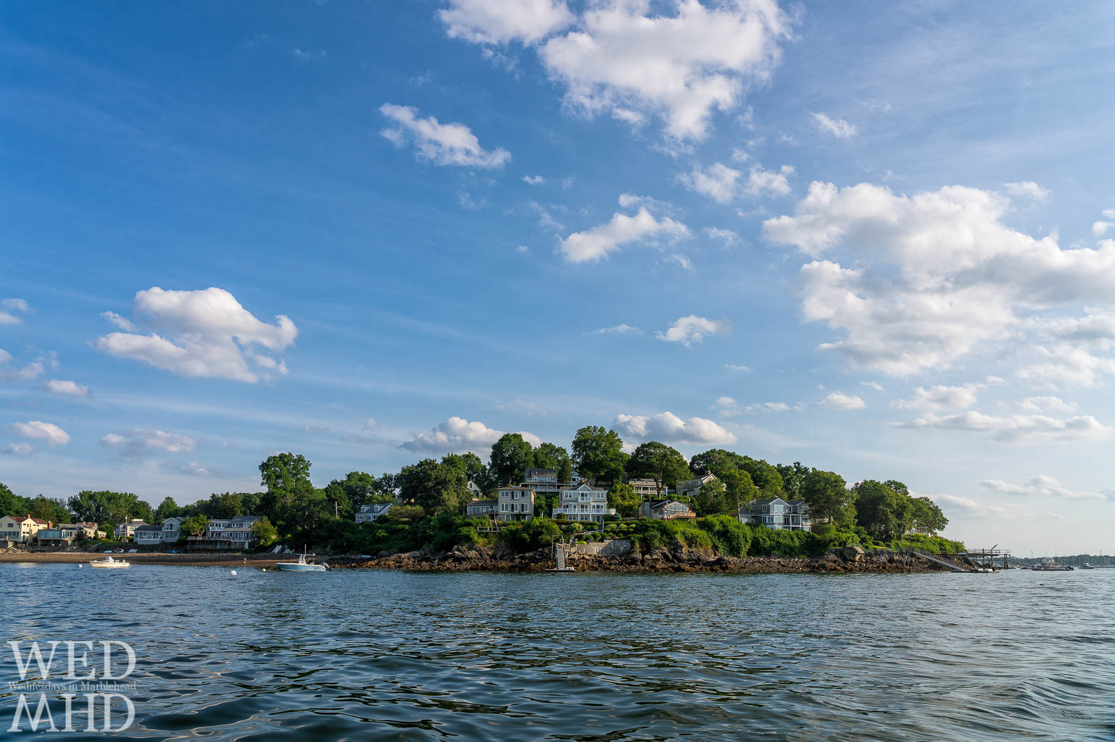 View of houses along Naugus Head in Marblehead from the water of Salem harbor on a warm summer evening