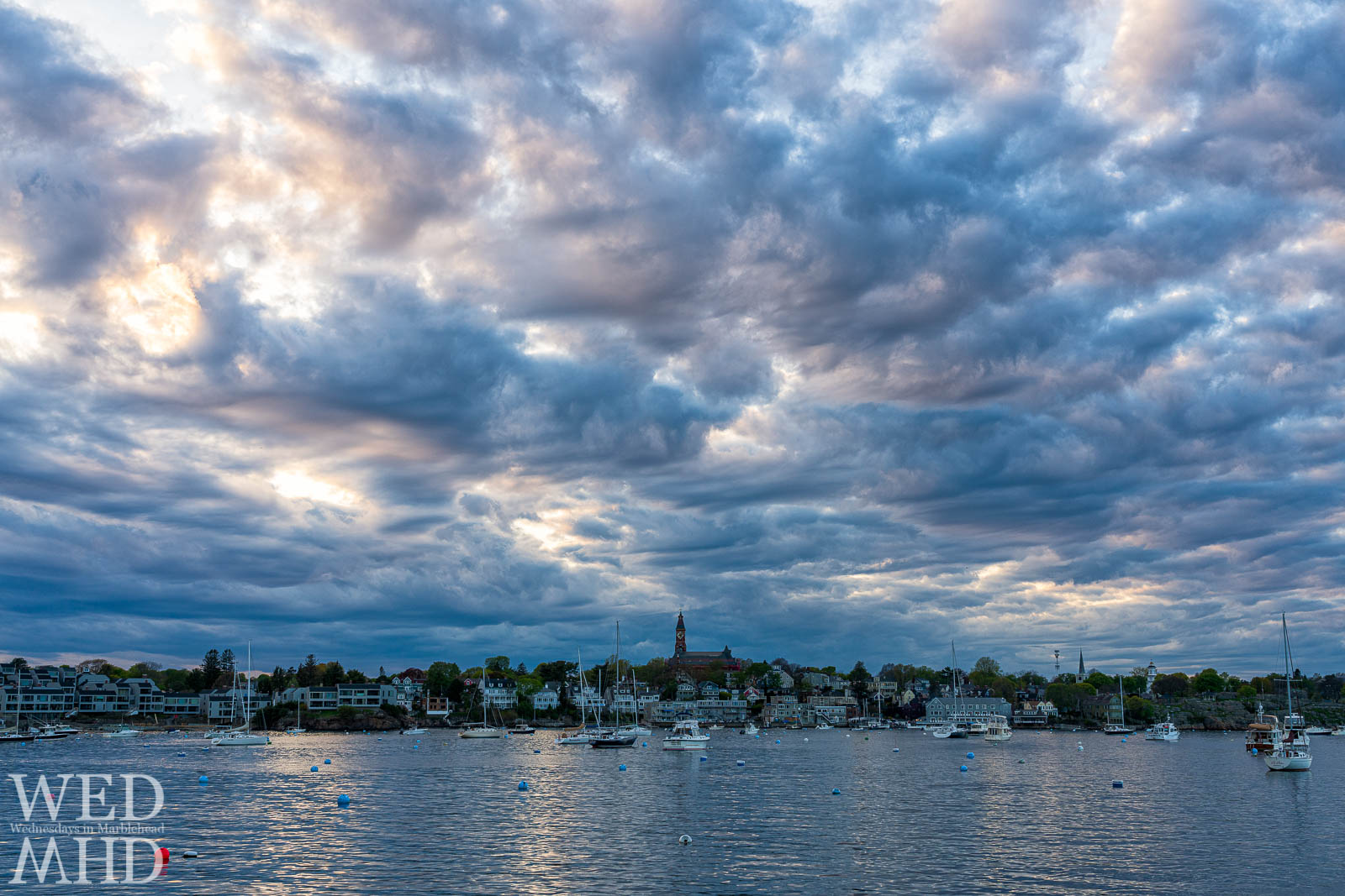 The sky above Marblehead appears to be painted with clouds on a mid-May evening with several boats already on their moorings