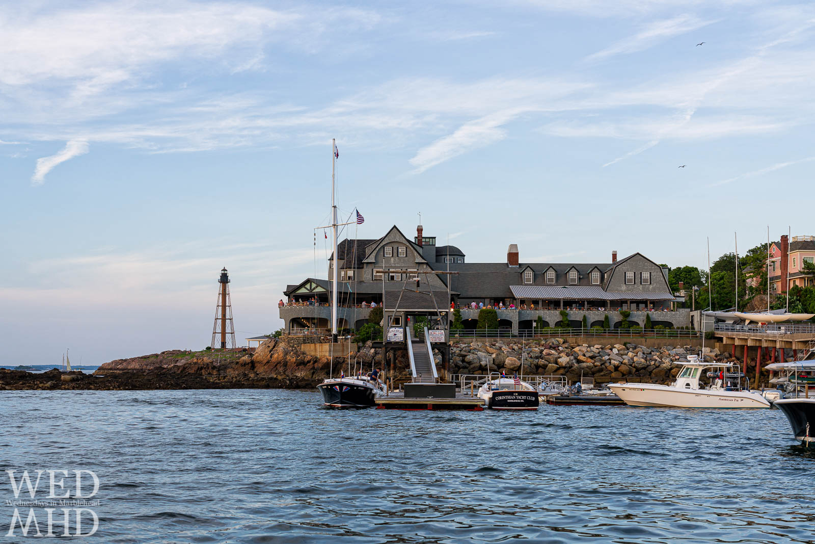 The Corinthian Yacht Club is packed on a Friday evening in the summer with Marblehead Light standing in close proximity from its spot on Chandler Hovey Park