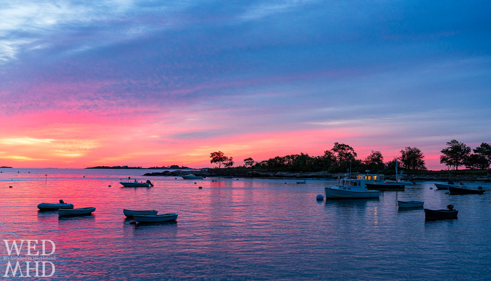 A pink sky reflects off the calm waters creating a beautiful First Harbor sunrise with one working boat ready to head out for the day