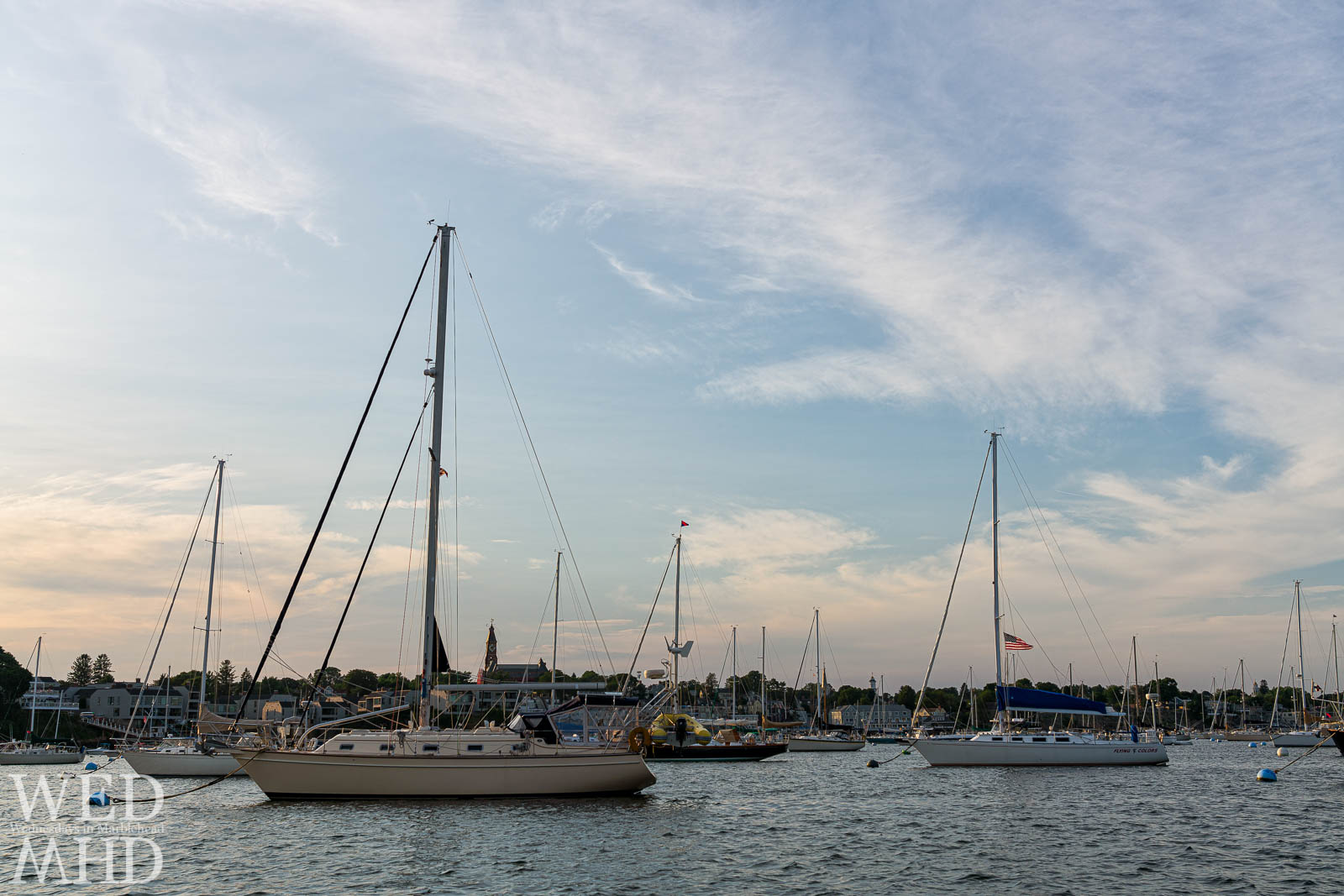A boat named Flying Colors is captured with the flag flying on a warm summer evening in Marblehead harbor