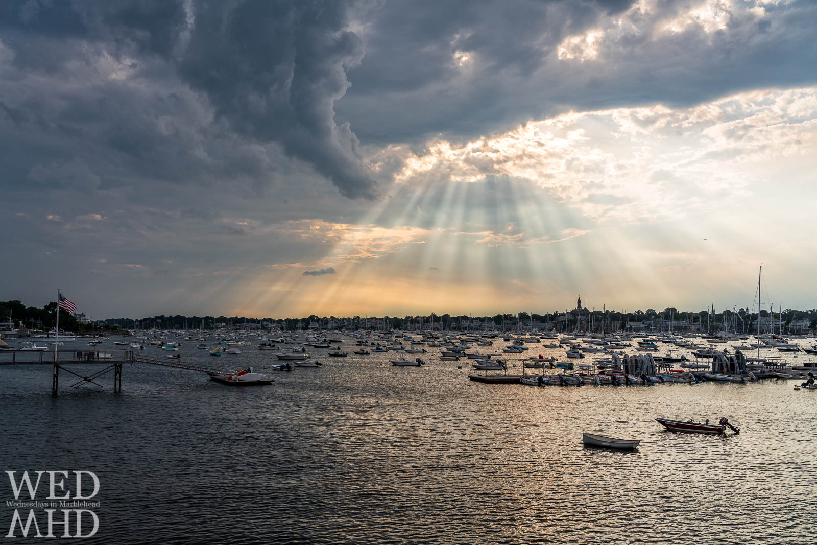 A full harbor and a flag flying at the end of a pier on the Neck are bathed by Marblehead Rays pouring through broken cloud cover
