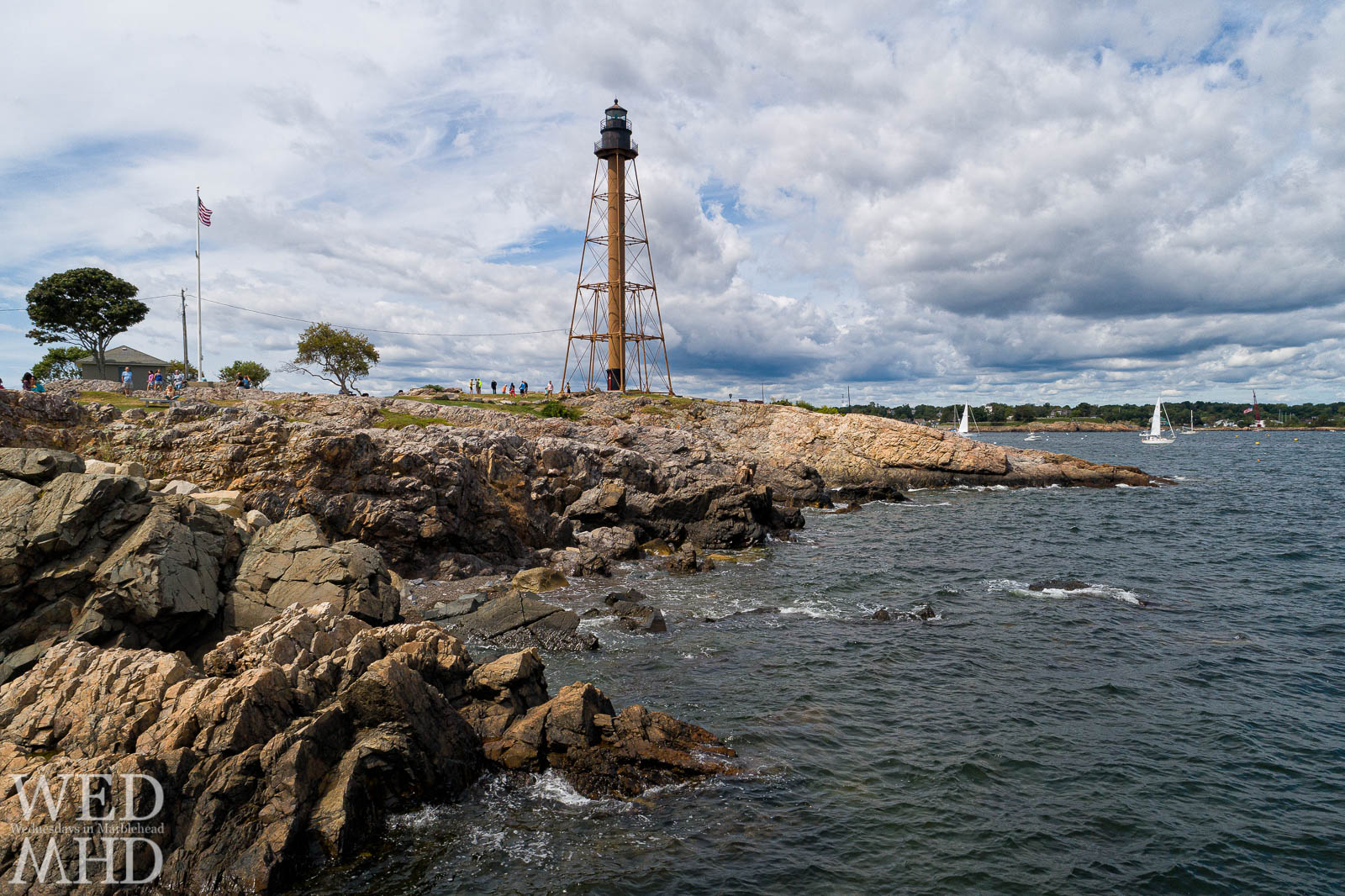 The rocky shores of Chandler Hovey Park lead towards Marblehead Light as seen from 20 feet above sea level and captured via drone
