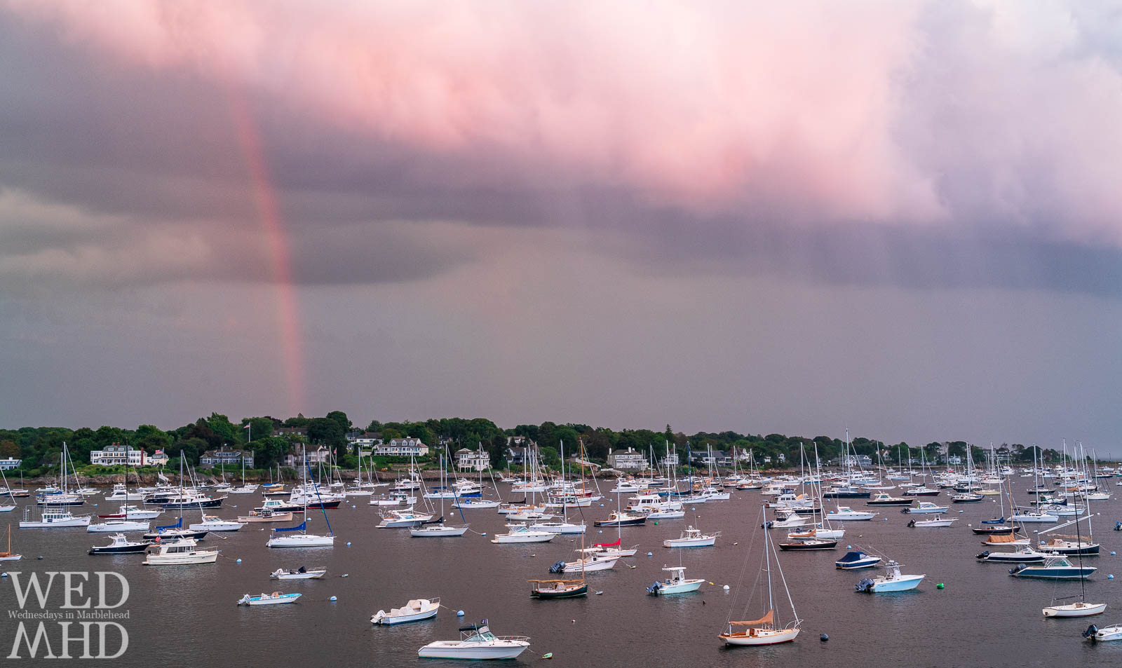 A sunset rainbow forms over Marblehead Harbor as a storm passes just as the sun set and lit the top of a cloud in pink light