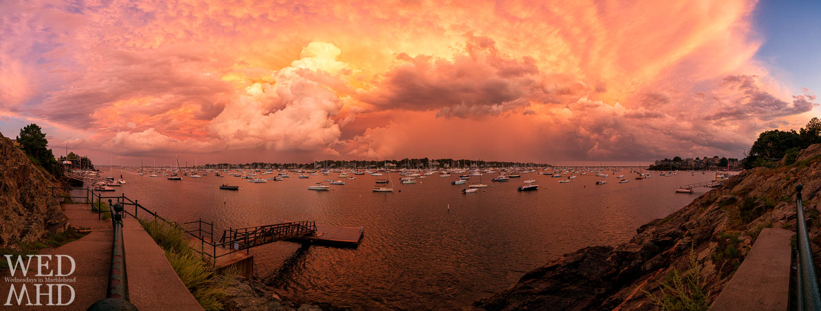 A storm passes and the creates this jaw-dropping view of an orange sky over Marblehead Harbor and the Neck with boats filling every mooring and the Crocker Park float leading the eye