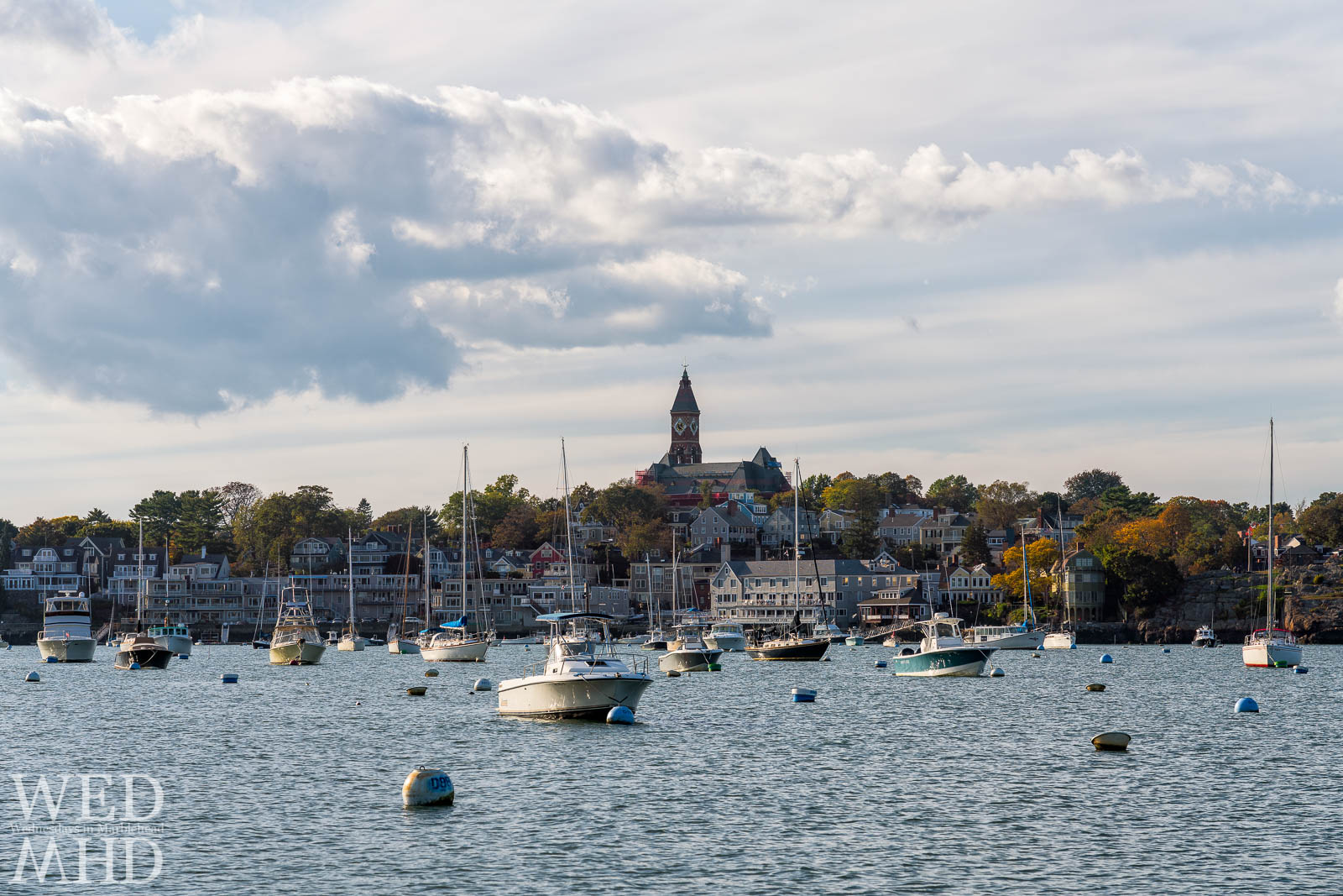Leaves change color across the harbor as the first signs of fall in Marblehead on a mid-October day with many boats still tied to their moorings