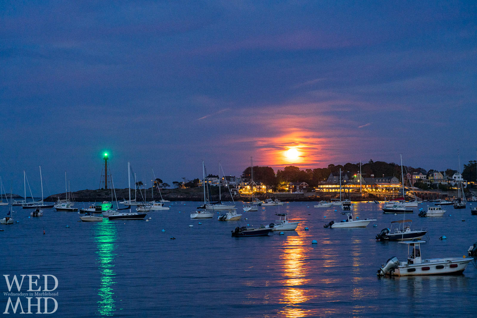 The Hunters moon rises over Marblehead Neck between the lighthouse and Corinthian Yacht Club on a mid-October evening