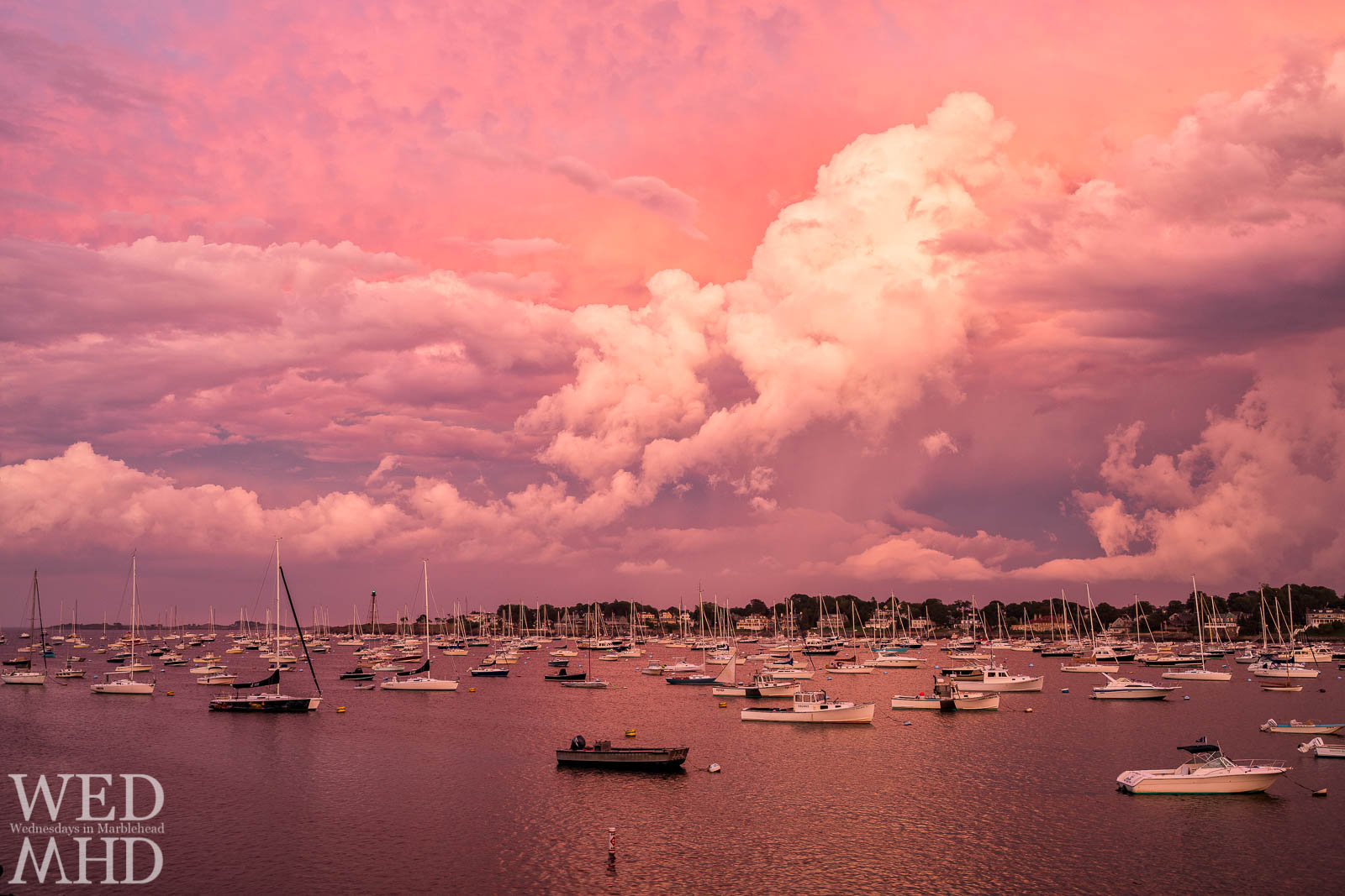 Clouds and light come together to form an incredible September sunset over Marblehead harbor with every mooring occupied by boats and the lighthouse beacon shining