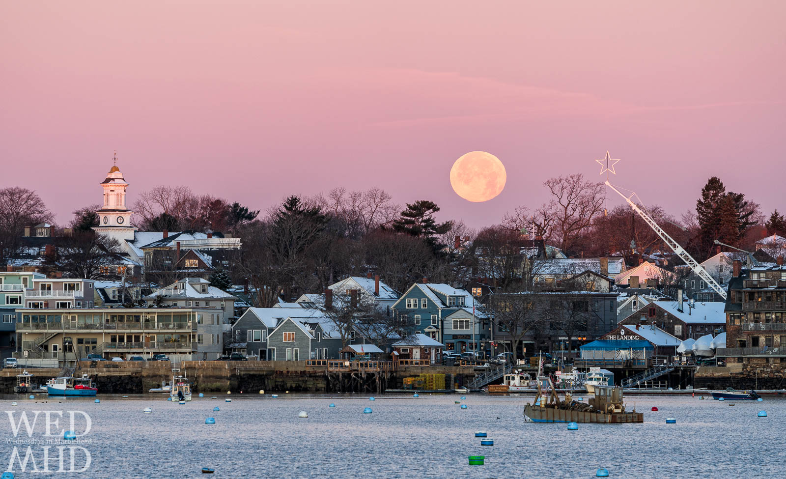 December's cold moon sets over State Street with a lit star suspended in the air and a nearly empty Marblehead harbor