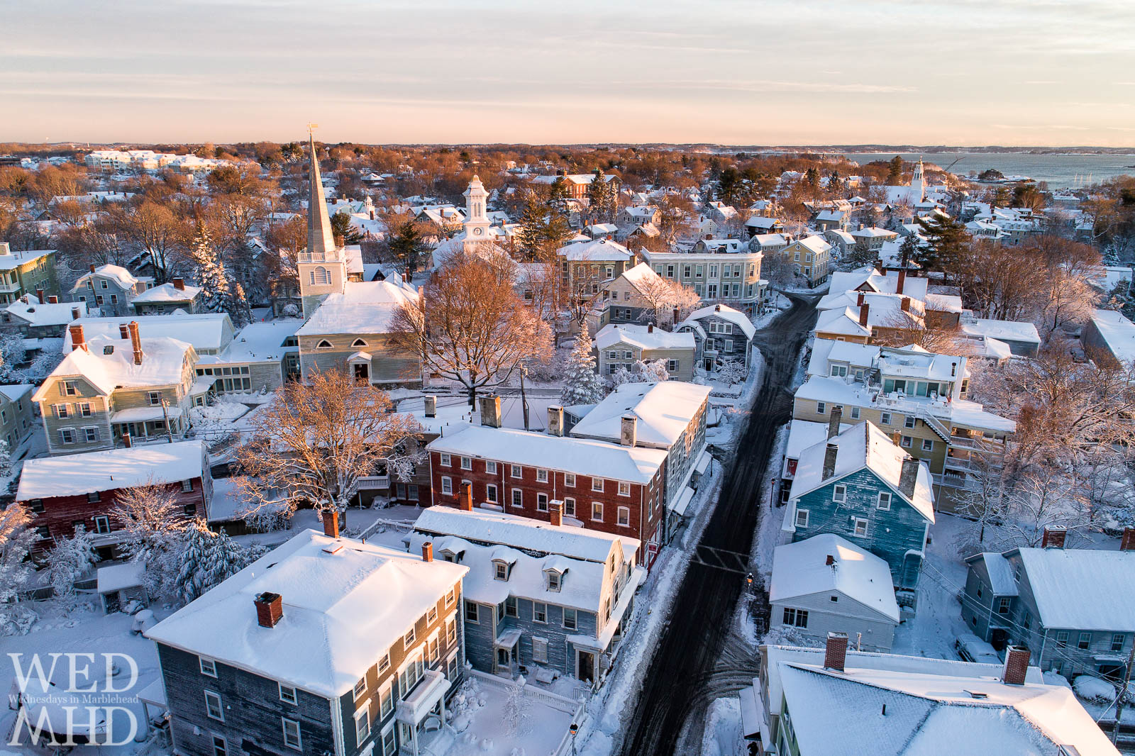 An aerial image of historic downtown Marblehead with a dusting of snow and early morning light
