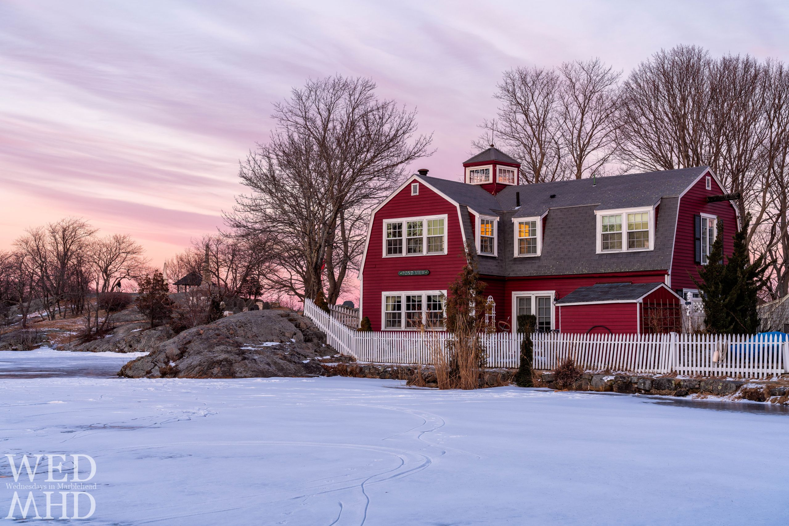 The red house named Pond View is captured at sunset with a light dusting of snow atop the frozen Redd's Pond