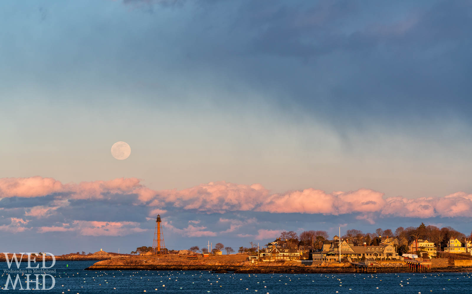 The full Snow moon rises over Marblehead Light and Childrens Island during a winter without snow