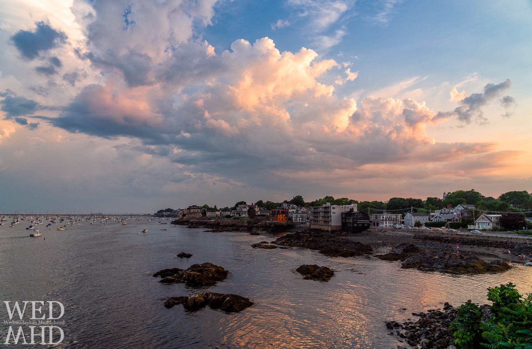 Sunset clouds reflect in the waters of Fort Beach on an early July evening in Marblehead
