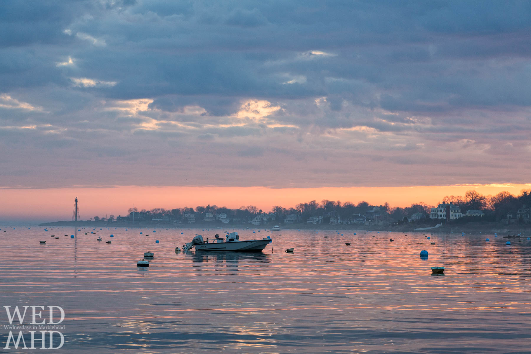 A lone Whaler moored in Marblehead Harbor and captured on a spring dawn with fog hovering over the water