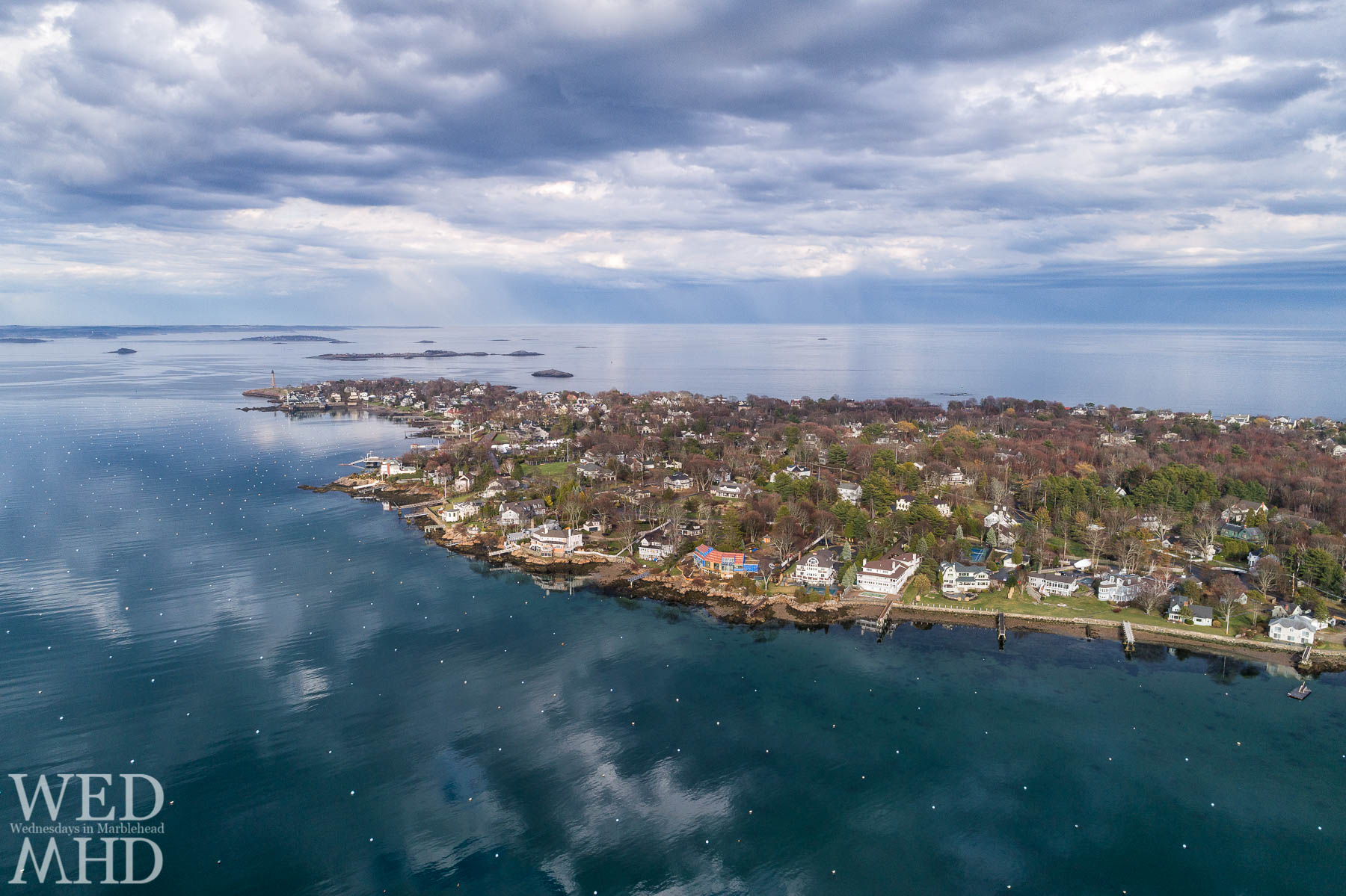 Aerial view of Marblehead Neck with clouds reflecting in the waters as the drone flies above an empty harbor