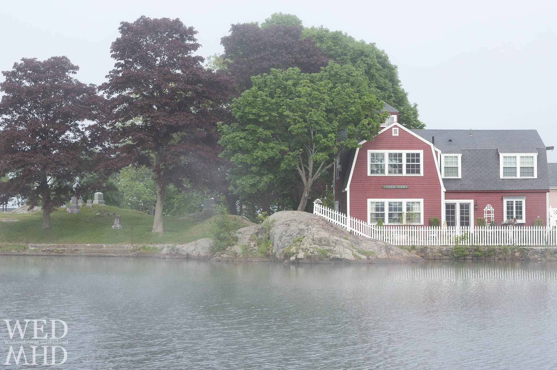 Fog builds at Redds Pond with the house named Pond View and its white picket fence reflecting in the water