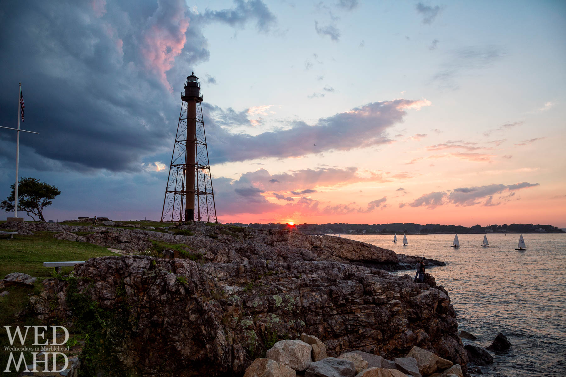 Sunset behind the lighthouse, fishermen on the rocks and boats in the harbor paint a perfect picture of summer nights in Marblehead