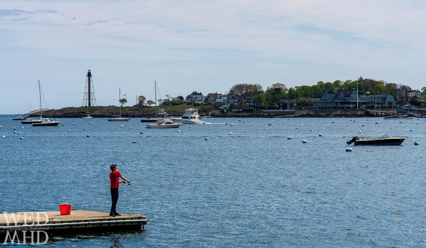 A young man wears a mask while fishing off of the State Street Landing in Marblehead