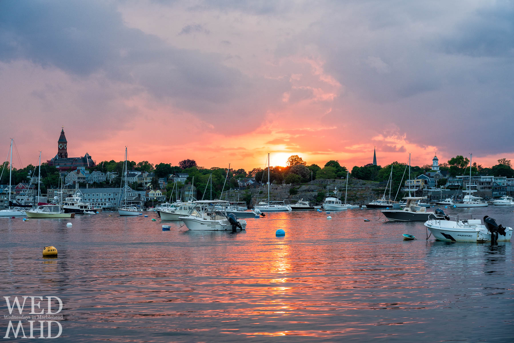 The sun sets behind Crocker Park and casts brilliant light onto the calm waters of Marblehead Harbor