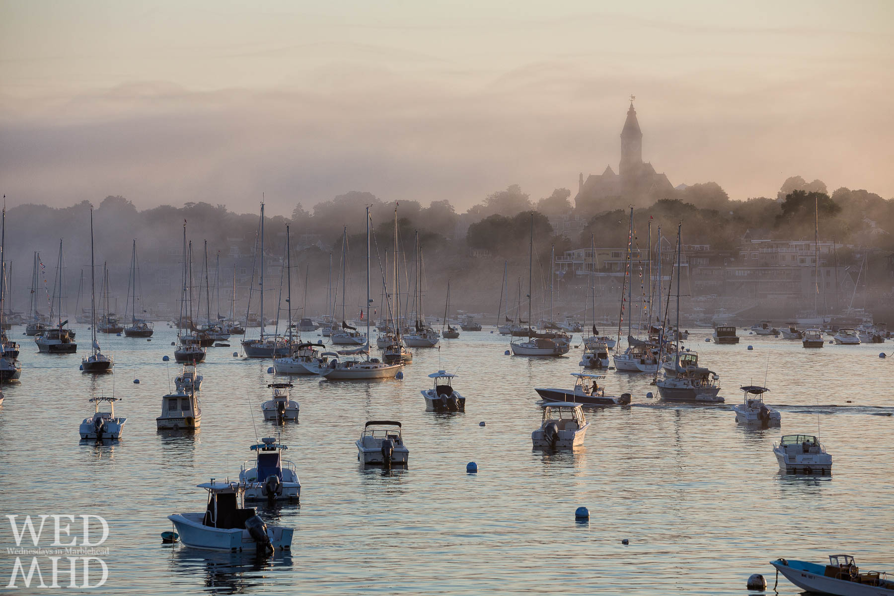 Summer bring foggy nights to Marblehead harbor with sunset coloring the fog in a warm pastel glow