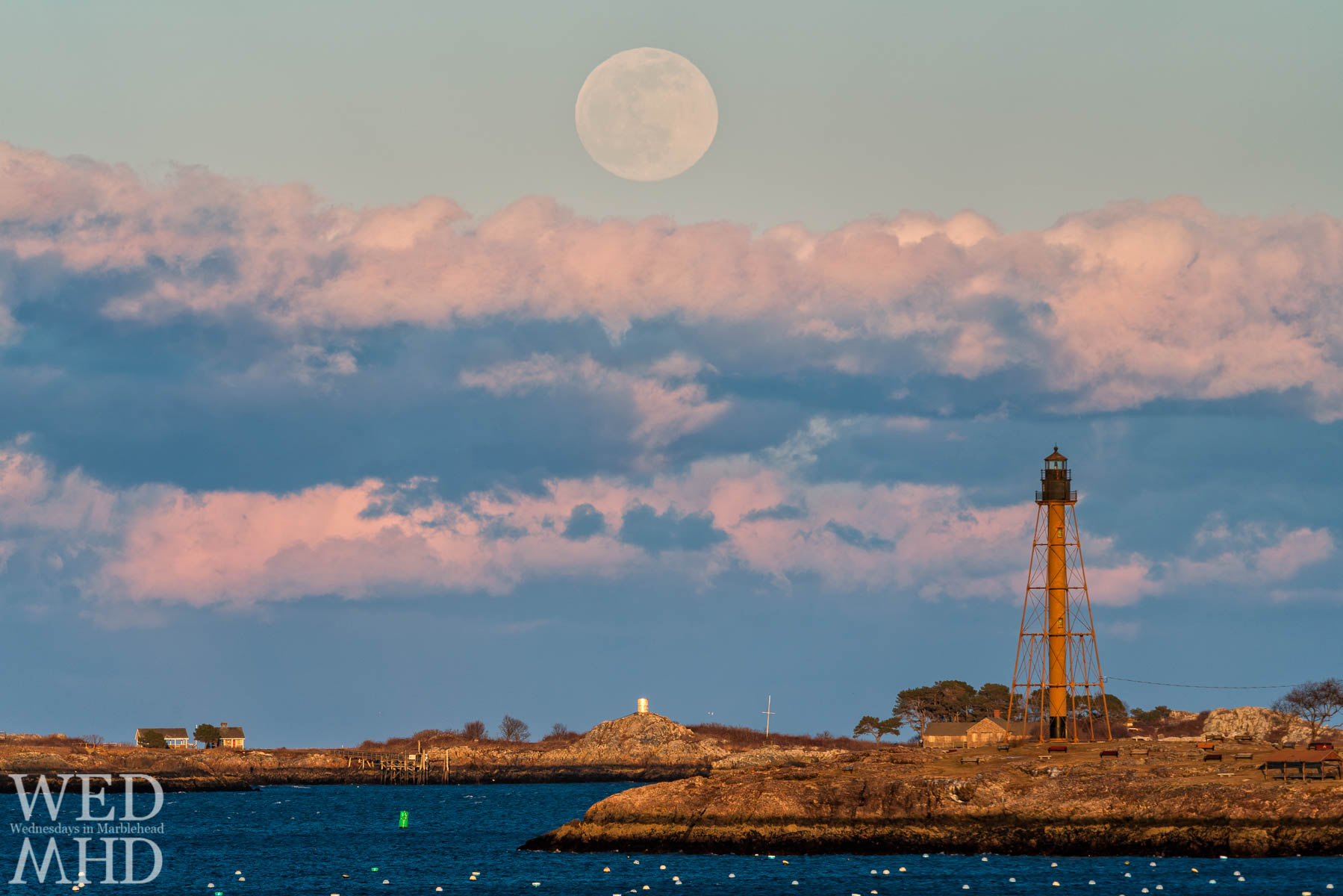 The moonrise over Marblehead light appears larger than life due to the use of a very long telephoto lens