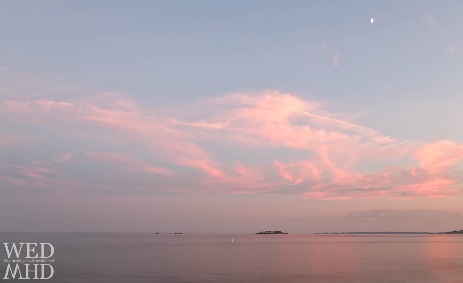 A moonlit sunset captured as a long exposure at Devereux Beach turns to ocean into still water and adds a soft reflection to the evening light