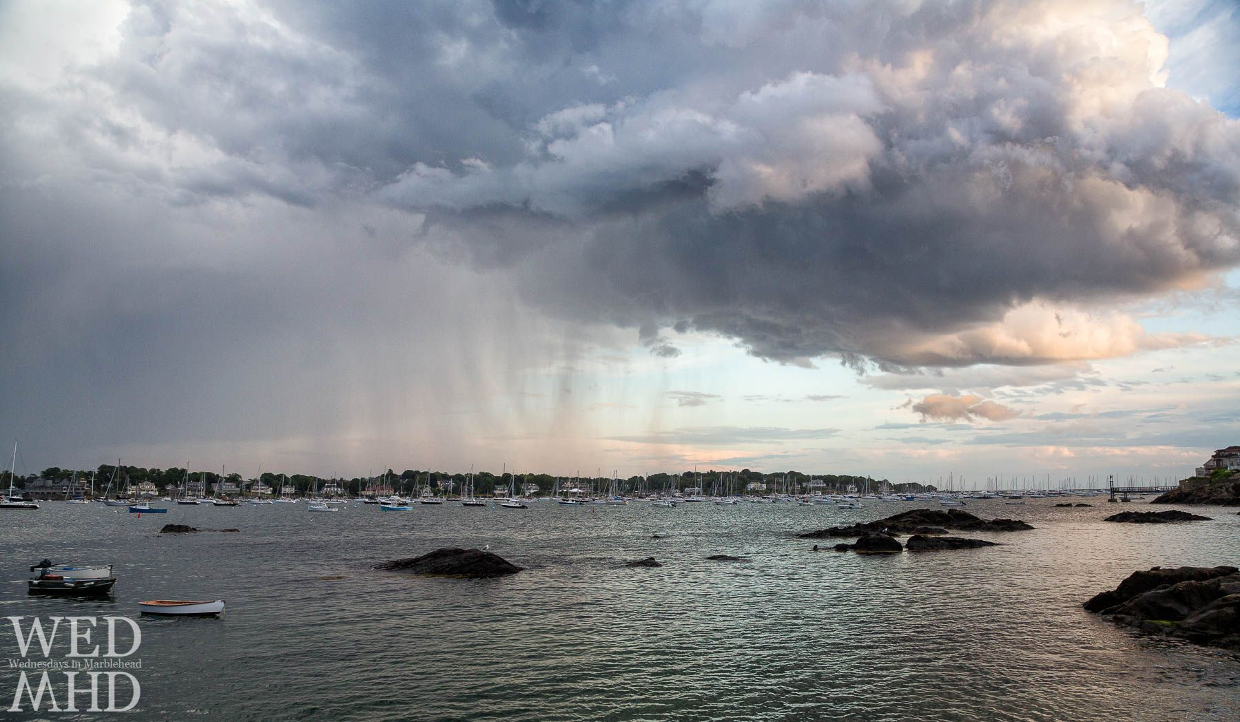 Rain falls over Marblehead Neck as passing showers form a dramatic scene over a harbor filled with boats