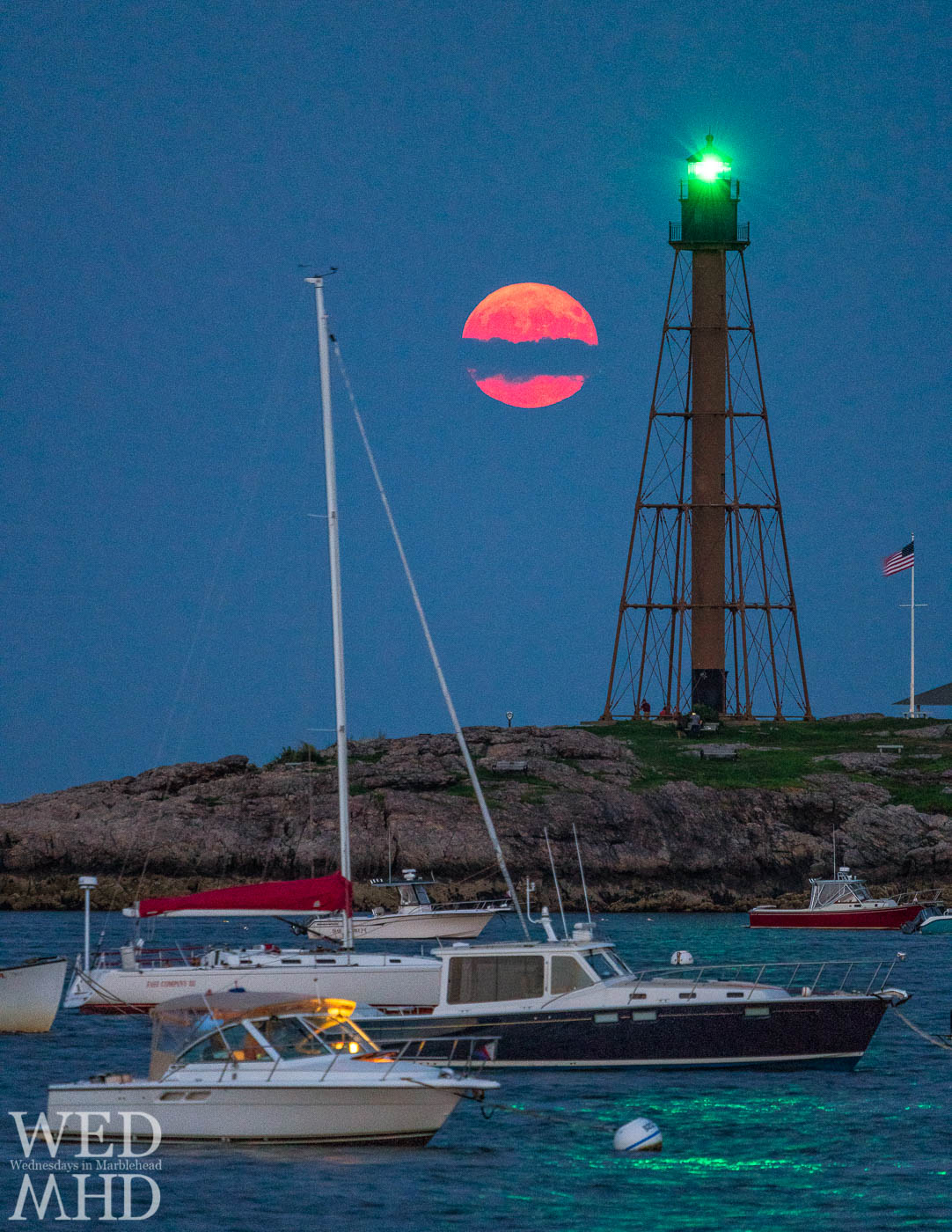 The moon rises through a band of clouds making it appear broken in half against the green glow of Marblehead Light