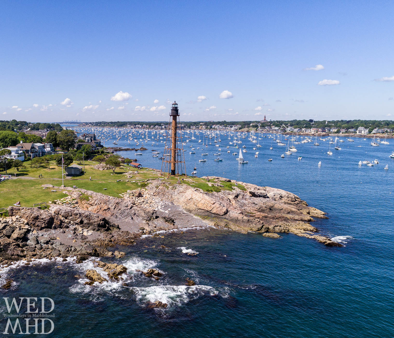 Marblehead Light stands tall on Chandler Hovey Park with the harbor full of activity behind it and Abbot Hall visible in the distance