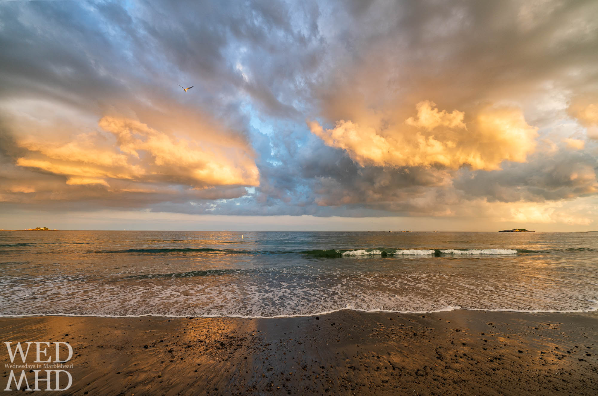 Sunset light reflects off the clouds above the Atlantic Ocean creating the illusion of a gold coast along Devereux Beach in Marblehead