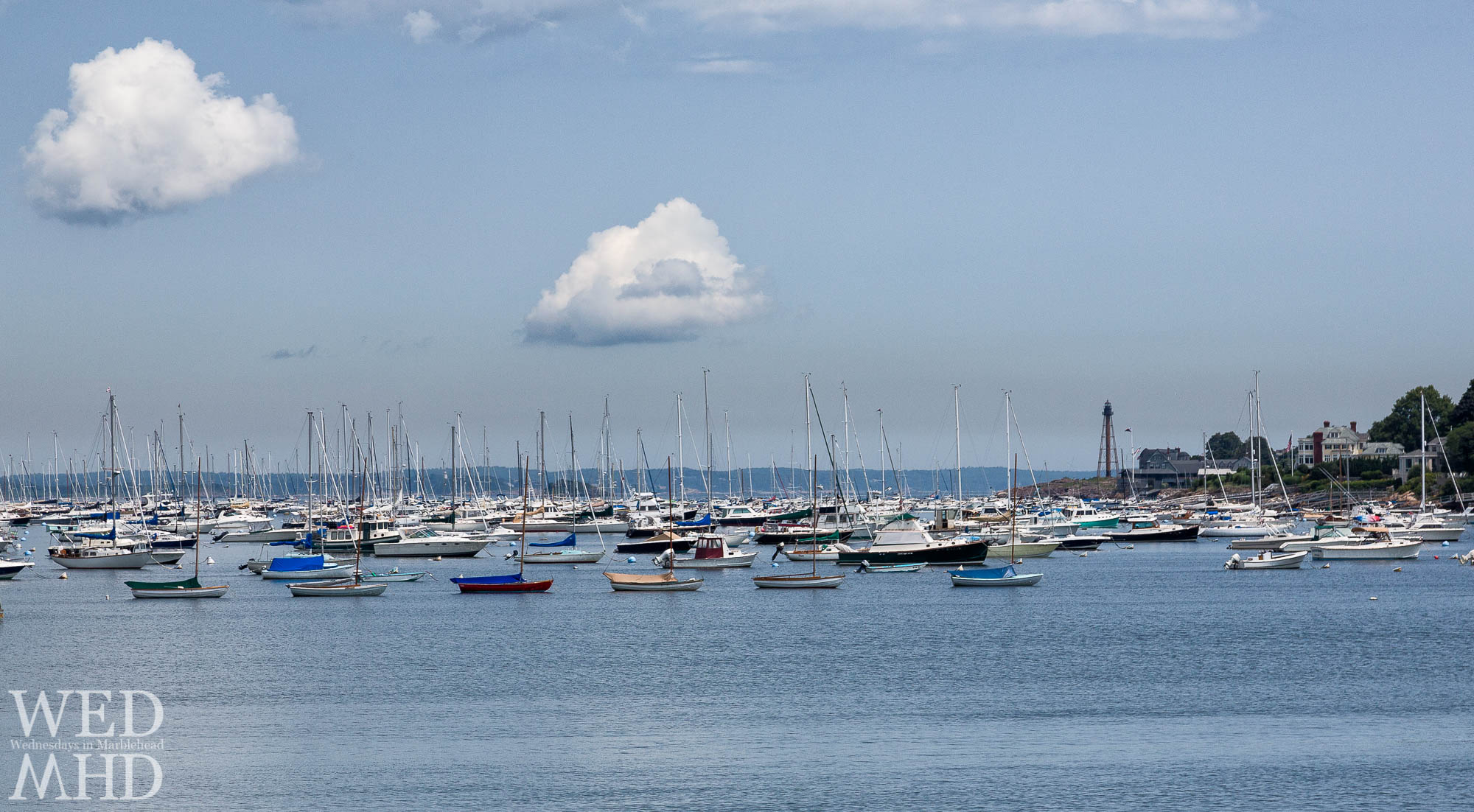 Two clouds over a full Marblehead harbor with town class sailboats in the foreground and Marblehead Light standing tall