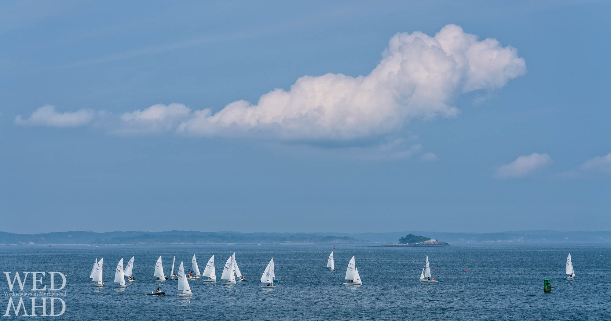 C420s sail in the waters off Marblehead Harbor with a few clouds overhead