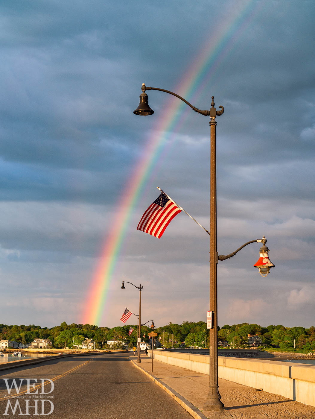 A rainbow forms at the end of the causeway and behind flags adorning each lamp post for the Fourth of July