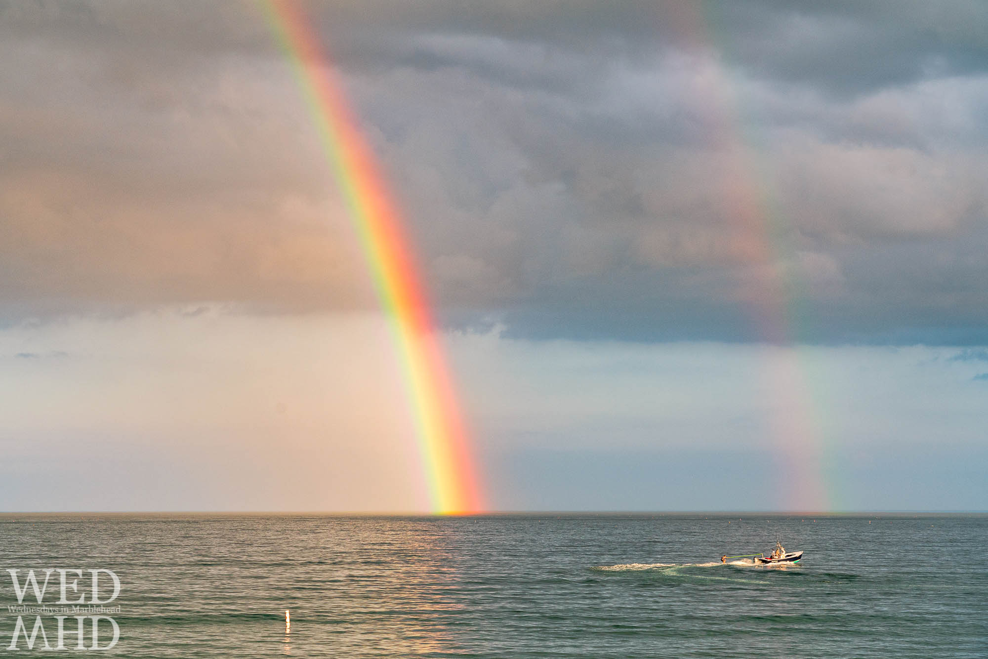 A family waterskis at the end of the rainbow on a late June evening off Devereux Beach in Marblehead