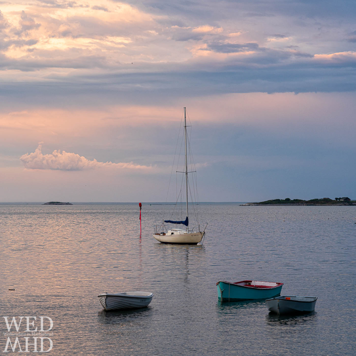 A dinghy named Liberty shares the calm water of Little Harbor with two others and a sailboat under soft sunset sky