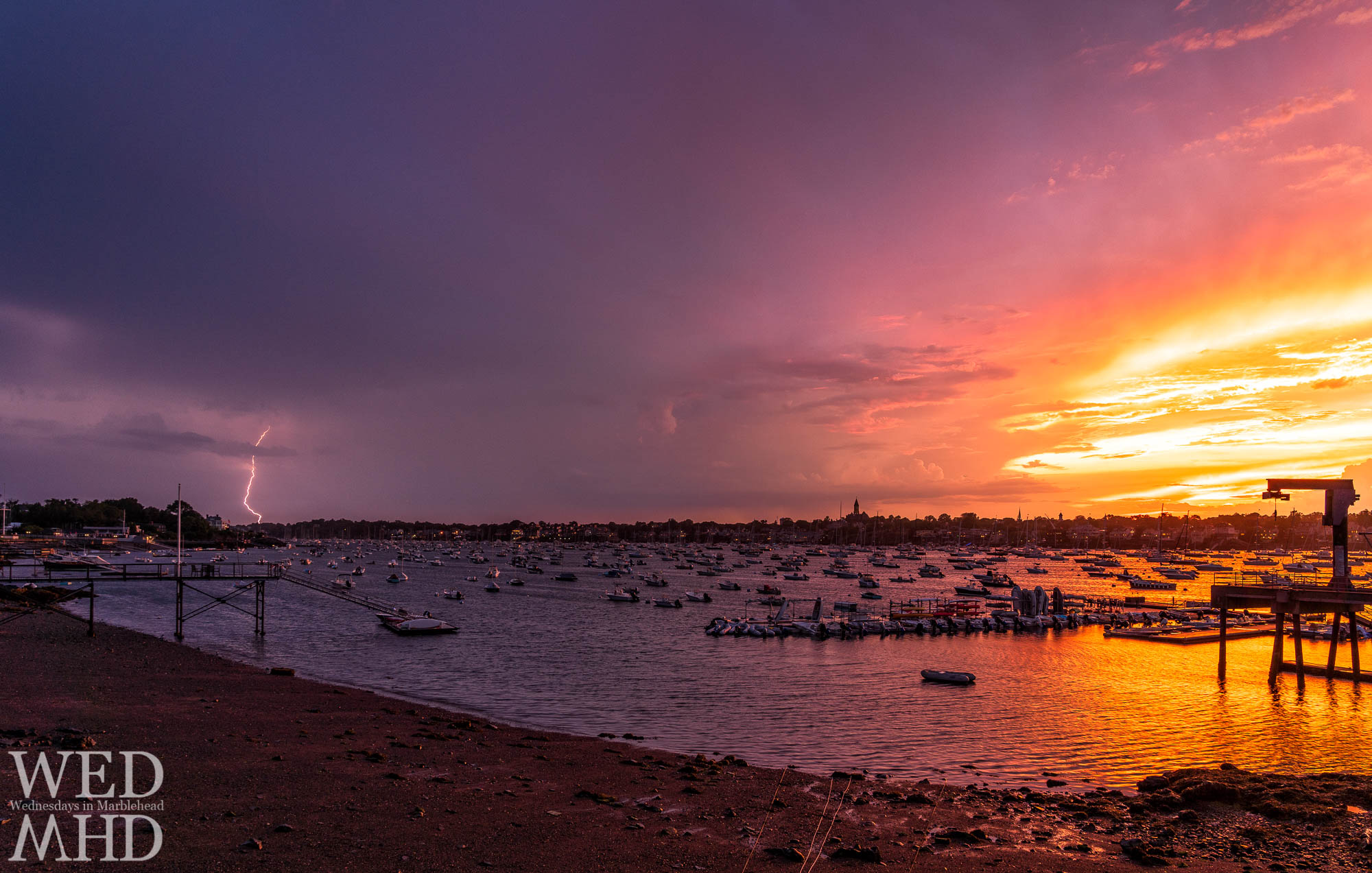 A bolt of lightning strikes during the peak of sunset in this view of Marblehead Harbor captured from Corinthian Lane