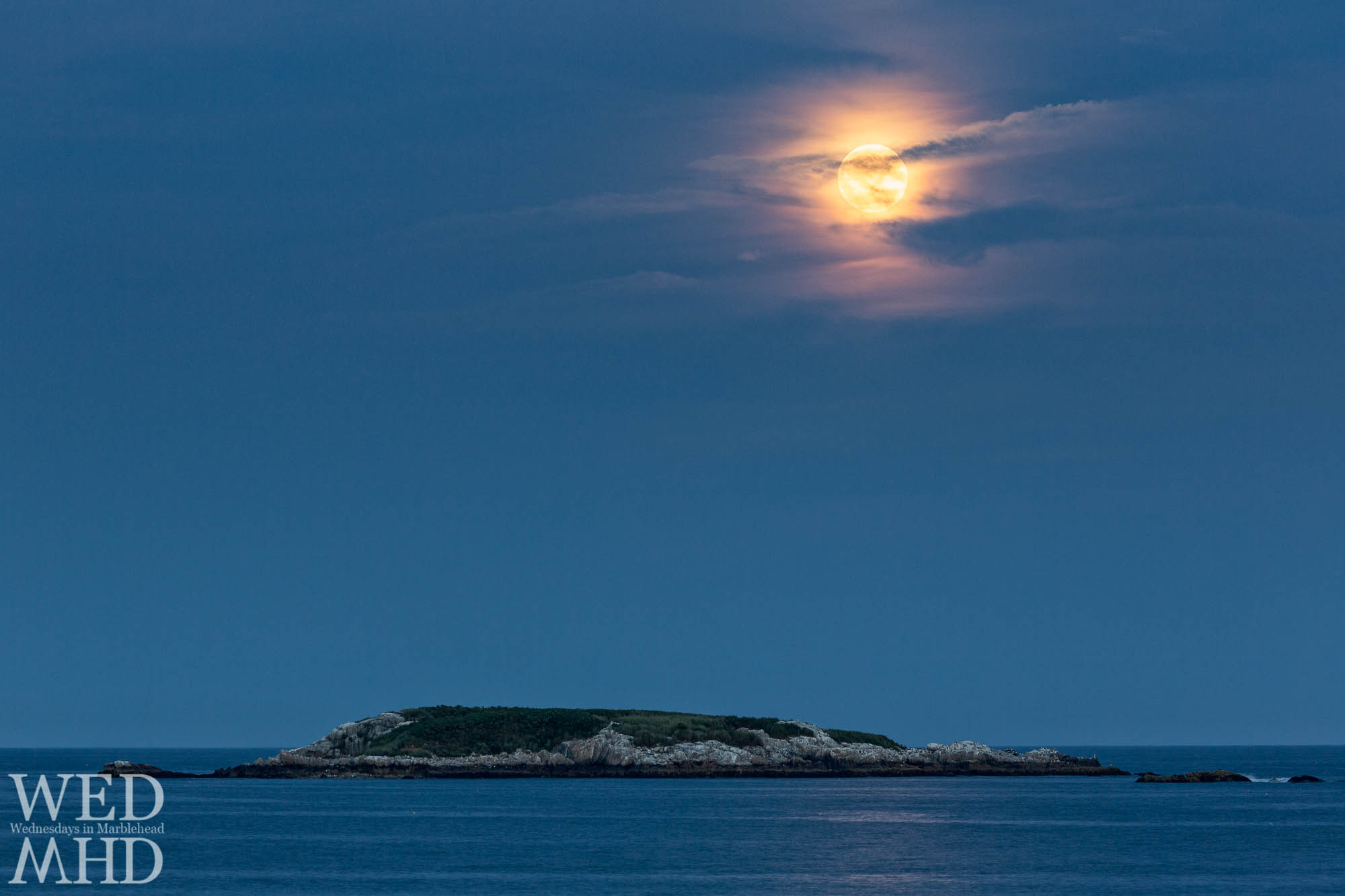 The full moon rises over Ram Island with cloud cover creating a moonglow effect in the evening sky